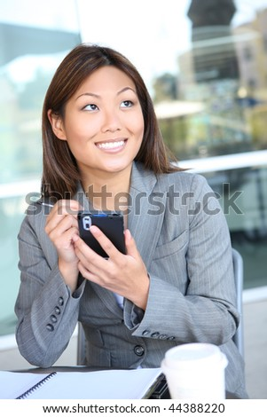 A young, pretty asian business woman texting  at work - stock photo