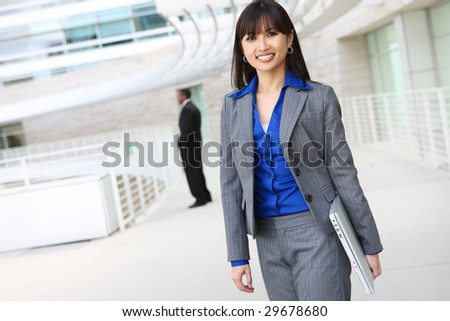 A young pretty asian business woman with laptop computer at work - stock photo