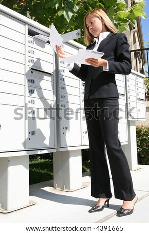 A young pretty business woman getting the mail from the mailbox - stock photo