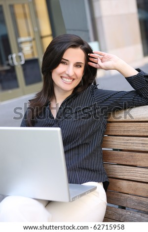 A young pretty business woman ouside office building with laptop cotmputer