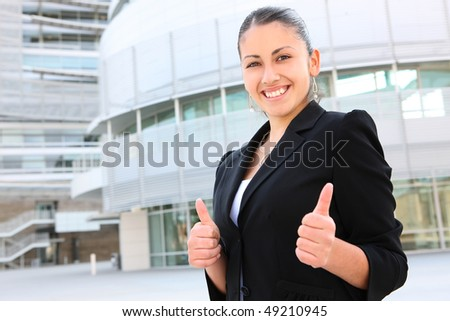 A young, pretty business woman outside an office building - stock photo