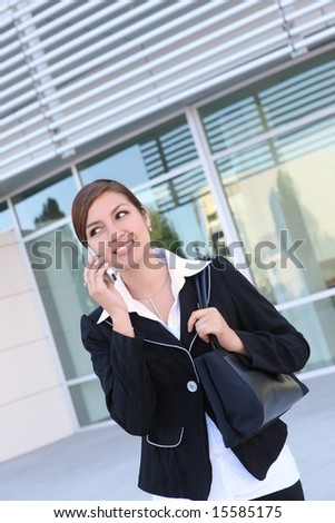 A young, pretty business woman outside an office building on Phone - stock photo