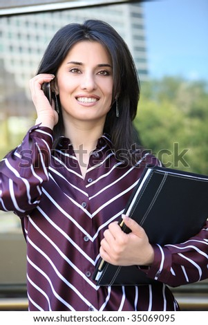A young pretty business woman outside office building on phone