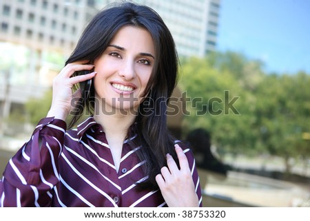 A young pretty business woman outside office building on phone - stock photo