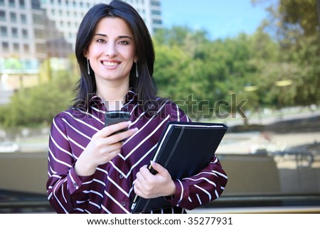 A young pretty business woman outside office building texting - stock photo