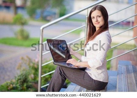 A young pretty business woman outside office building with laptop compute - stock photo