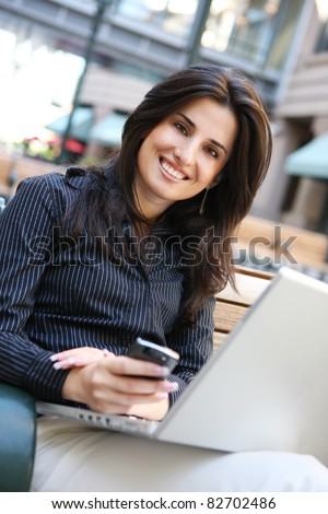 A young pretty business woman outside office building with laptop computer and smartphone