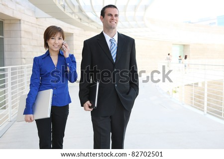 A young pretty business woman outside office building with laptop computer and smartphone - stock photo