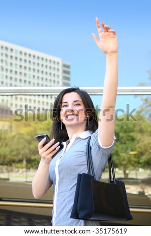 A young pretty business woman waving goodbye at office building - stock photo
