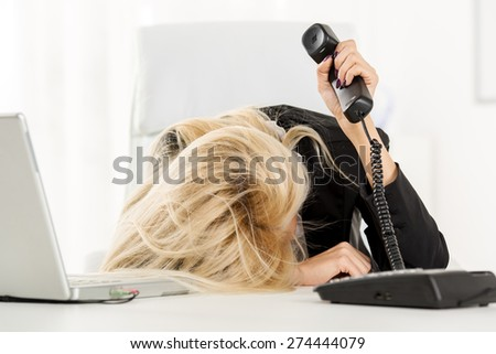 A young pretty businesswoman, exhausted from work sleeping in front of her laptop, leaning on office desk with a telephone handset on hand. - stock photo