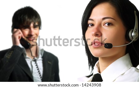 A young pretty call center woman and a young operator guy are smiling and they are talking to their clients using headphones and wire phone. They are wearing elegant shirts.