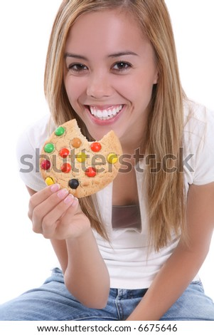 A young pretty girl eating a chocolate chip cookie dessert