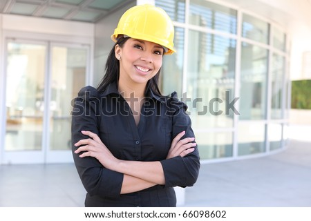A young pretty hispanic woman architect with at building work site - stock photo