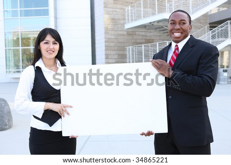 A young pretty indian business woman and african man holding a sign - stock photo