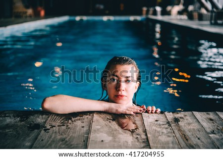A young pretty woman relaxes in the swimming pool. Wellness concept. Spa and relax, woman happiness. - stock photo