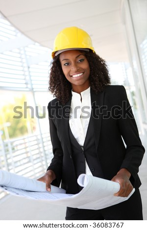 A young pretty woman working as architect on a construction site - stock photo