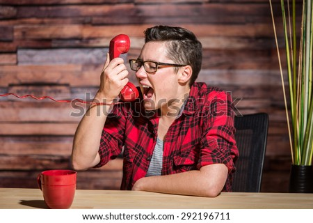 A young professional woman screams into red phone - stock photo