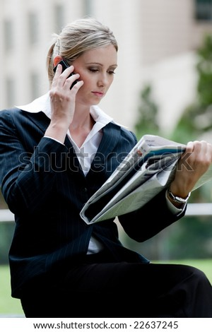 A young professional woman sitting outside reading the newspaper - stock photo