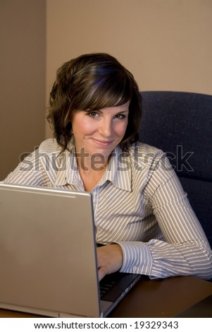 A young professional woman working on a laptop - stock photo
