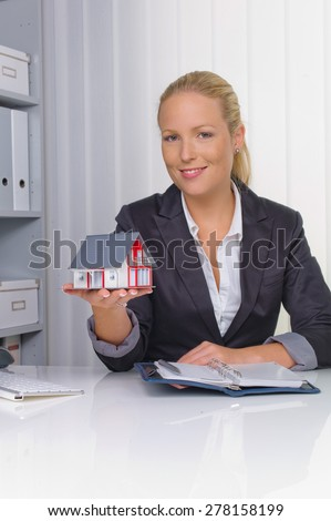 a young real estate agent with a model house in her office. - stock photo
