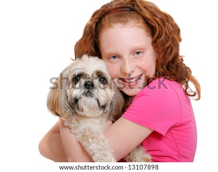 a young red haired girl holding her dog close over white