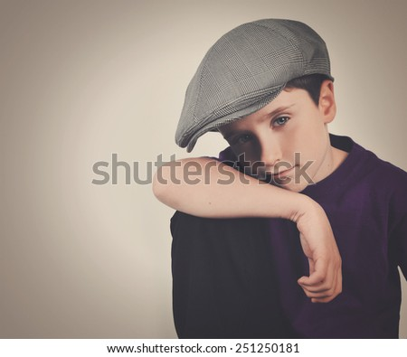 A young retro boy is wearing a driving cap hat and posing with his hand on his knee. There is an isolated background to add your message. - stock photo