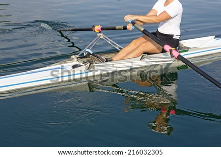 A young rower in a boat, paddles on the tranquil lake - stock photo