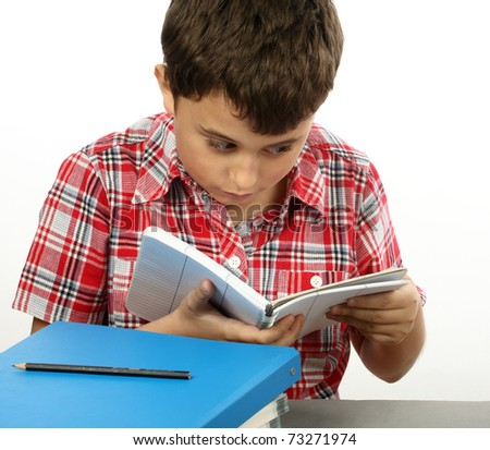 A young schoolboy reading a  book - stock photo