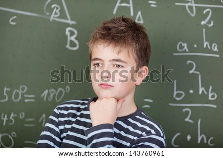 A young schoolboy thinking about something, standing near the blackboard in mathematics class. - stock photo