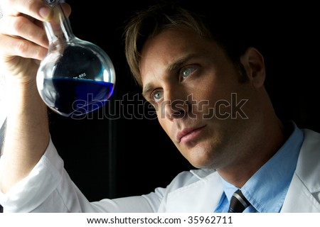 A young scientist conducting an experiment in a lab - stock photo