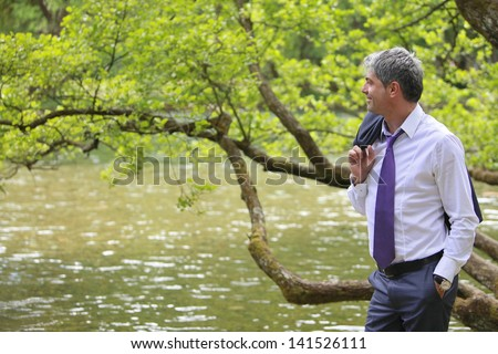 A young self-confident businessman standing in the nature, near a river and looking to the distance.../My success are my efforts - stock photo