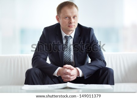 A young serious businessman in suit looking at camera - stock photo