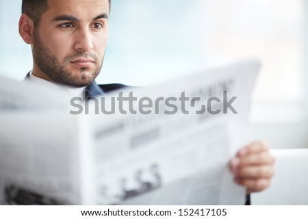 A young serious businessman reading newspaper - stock photo