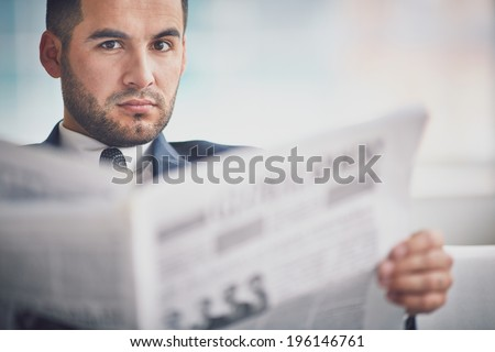 A young serious businessman with newspaper looking at camera - stock photo