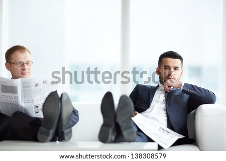 A young serious businessman with newspaper looking at camera with his colleague reading news near by