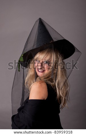 a young sexy woman dressed as a witch, makeup for Halloween - stock photo