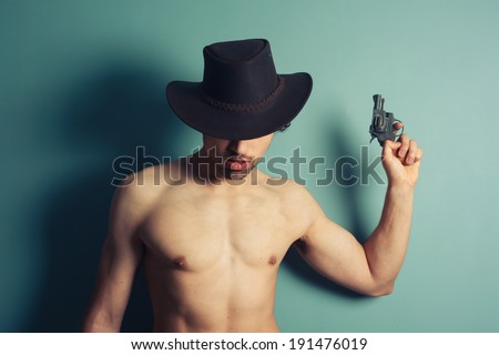 A young shirtless cowboy is holding a revolver - stock photo