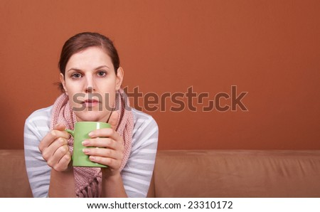A young sick woman with a cup of tea in her hand. She hold her head in pain. A lot of copyspace. - stock photo