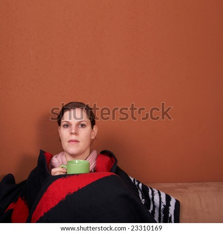 A young sick woman with a cup of tea in her hand. With a lot of copyspace. - stock photo