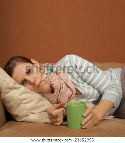 A young sick woman with a thermometer in her mouth and with a cup of tea in her hand. With a lot of copyspace. - stock photo