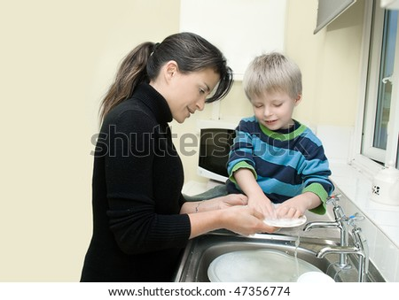 A young single mother and child washing dishes together. - stock photo