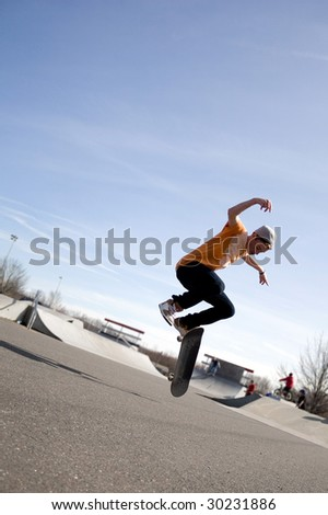 A young skateboarder doing a stunt in a skate park. - stock photo