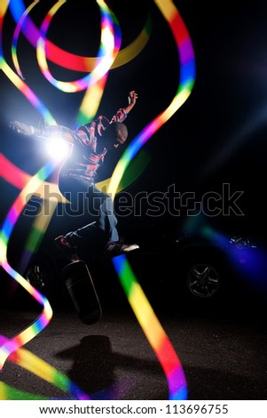 A young skateboarder doing jumping and kick flip tricks under dramatic rim lighting with lens flare and colorful rainbow light trails. - stock photo