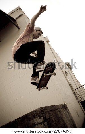 A young skateboarder launches off a concrete loading dock in an urban setting. - stock photo