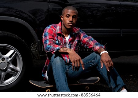 A young skater hanging out seated on his skateboard next to a parked car. - stock photo