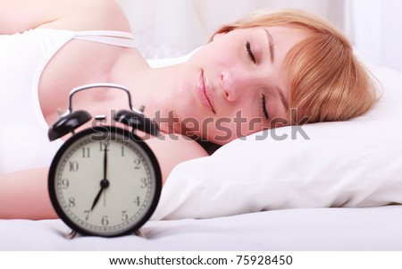 A young sleeping woman and alarm clock in bedroom