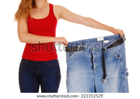 A young slim woman in jeans holding her old big jeans after she lost much weight, isolated for white background.  - stock photo