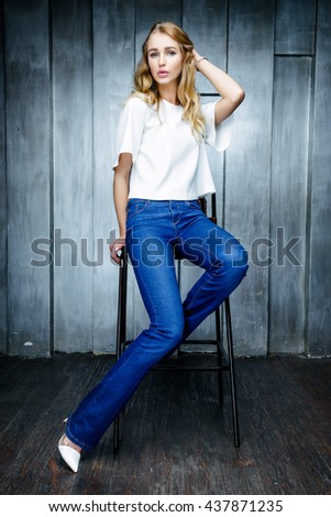A young slim woman wearing white blouse posing  in the room. - stock photo
