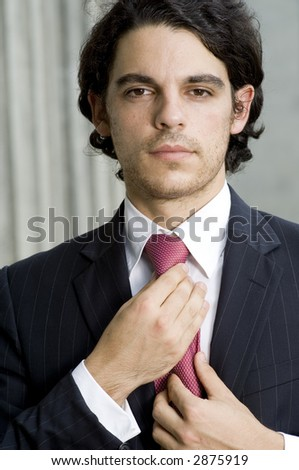 A young smartly dressed businessman holding tie