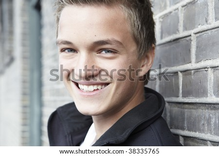 a young smiling boy in a schoolyard - stock photo
